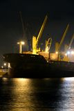 The loading cargo ship with cranes is moored in port at night Stock Photography