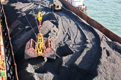 Loading coal from cargo barges onto a bulk carrier using ship cranes and grabs at the port of Samarinda, Indonesia. View of a close-up of the work of stock photo
