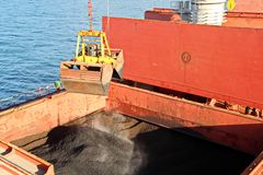 Loading coal from cargo barges onto a bulk carrier using ship cranes and grabs at the port of Samarinda, Indonesia. stock photography