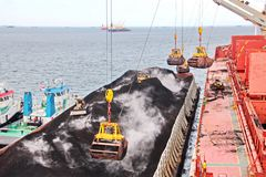 Loading coal from cargo barges onto a bulk carrier using ship cranes and grabs at the port of Samarinda, Indonesia. royalty free stock image