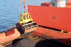 Loading coal from cargo barges onto a bulk carrier using ship cranes and grabs at the port of Samarinda, Indonesia. royalty free stock photo