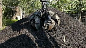 Loading of coal a truck using a hydraulic gripper. Loading of coal a truck using a hydraulic excavator with gripper,slow motion video clip stock footage