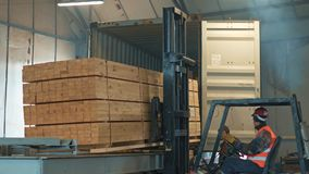 Loading container a bundle with timber. Trucks transporting blocks of wood stock video