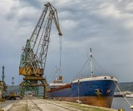 At the city port. Loading container or raw materials in the warehouse on the trading ship of the port city, Varna, Bulgaria royalty free stock photo