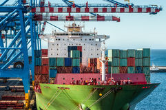 Loading Container Ship. Shipping Transportation Industry - containers are load on board a ship by cranes. Closeup cargo ship and portal action Stock Images
