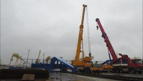 Loading of containers with cargo trucks at the industrial zone on grey, cloudy sky background. Automobile cranes in a stock video footage