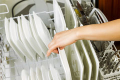 Loading dinner plates into the lower dish rack of dishwasher Stock Photography