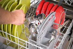 Loading dishwasher. Close-up of female hands lodaing dirty dishes to the dishwashing machine stock photography