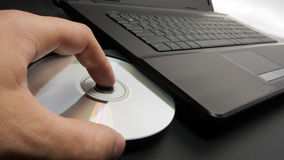 Loading disk into laptop Stock Photo
