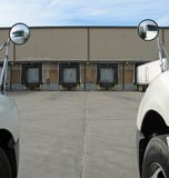 Loading Dock doors. View of loading docks from across a parking between two trucks Royalty Free Stock Photography
