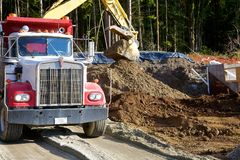 Loading a dump truck. A backhoe loading up a dump truck with dirt at a construction site royalty free stock image