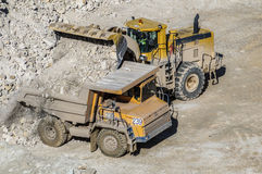 Loading of gypsum in mining truck. Dump truck loads mining truck in the career of mining of gypsum Stock Images