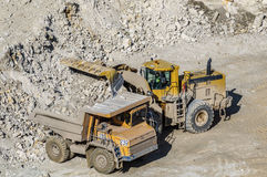 Loading of gypsum in mining truck. Dump truck loads mining truck in the career of mining of gypsum Royalty Free Stock Image