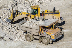 Loading of gypsum in mining truck. Dump truck loads mining truck in the career of mining of gypsum Royalty Free Stock Photo