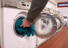Loading laundry machine. Hand in green sleeve is loading washing machine Stock Photo