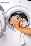Loading laundry to the washing machine. Hand loading laundry to the washing machine Stock Photos