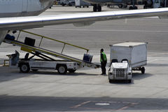 Loading luggage. Personnel loading luggage into a plane in an airport Royalty Free Stock Image