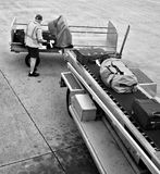 Loading luggage onto plane B/W. A man is loading luggage onto airplane - black and white version Royalty Free Stock Photos