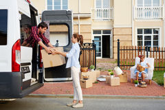 Loading the Moving Van. Portrait of young women helping her husband load cardboard boxes into moving van while their daughter waiting with other belongings in Stock Photography