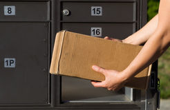 Loading package into Mailbox. Closeup horizontal front view of female hands putting package into postal mailbox with green grass and sidewalk in background Stock Photography