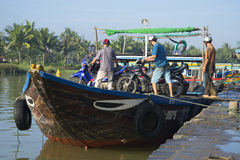 Loading people and small-sized vehicle on a river ferry in the town of Hoi An, Vietnam Royalty Free Stock Photography