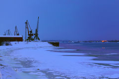 Loading pier with cranes on river at night in winter Stock Photos