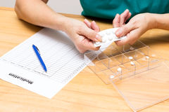 Loading a pill organizer Stock Photos