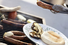 Loading the Plate. Loading a plate with the cooked items from the Sausages, onion slices and pita bread that are getting ready on an outdoor barbecue grill Royalty Free Stock Images