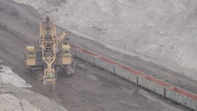 Loading rail cars a bucket wheel excavator for mining. Extraction and shipment takes place with help of rotary excavator, a machine for longitudinal digging stock video