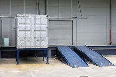 Loading Ramp Container. Loading Ramp and Silver Shipping Container in Front of Warehouse Royalty Free Stock Photography