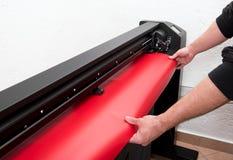 Loading red film on plotter Stock Photo