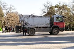 Loading rubbish into a garbage truck in a public park on a spring day. Waste disposal and cleanliness royalty free stock images