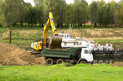 Loading sand excavating in the car body on the riverbank Royalty Free Stock Images