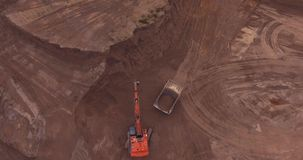 Loading sand excavating in heavy trucks. Flight to drone on sand quarry with heavy machinery, the old truck and excavator. loading sand excavating in heavy stock footage