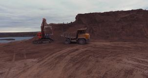 Loading sand excavating in heavy trucks Flight to drone. Flight to drone on sand quarry with heavy machinery, the old truck and excavator. loading sand stock video footage