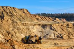 Loading sand with a wheeled front loader with a large bucket into a heavy dump truck. In opencast mining stock photos