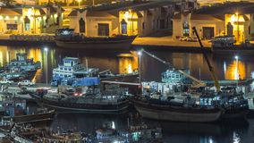 Loading a ship in Port Said night timelapse in Dubai, UAE. Loading a ship in Port Said night timelapse in Dubai, Deira creek, UAE. Aerial top view from above stock video footage