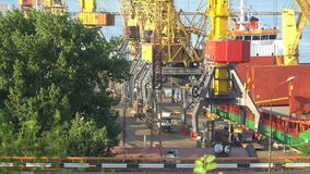 Loading a ship in the seaport. Securing cargo to the crane stock footage