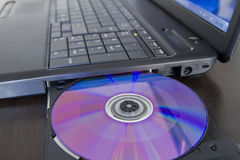 Loading software into a laptop. Laptop with a cd in the tray royalty free stock photo