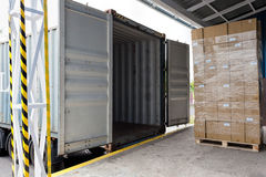 Loading the truck. Forklift with carton boxes loading the truck Stock Photo