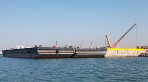 Loading of two cargo barges in port Stock Photos