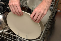 Loading or unloading dishwasher Royalty Free Stock Image