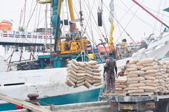 Loading/unloading goods. A group of workers are loading/unloading goods onto/from ship at harbour Stock Photos