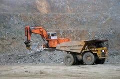 Loading up. Digger loading up trucks with rock at Stockton Coal Mine, Westland, New Zealand Royalty Free Stock Photography