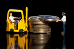 Loading Up Euros. Miniature workmen with a forklift load up a pile of Euro coins for removal, macro on black with reflection Stock Photography