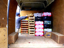 Loading a van with fresh food. A Market trader loading/unloading a white delivery van Royalty Free Stock Image