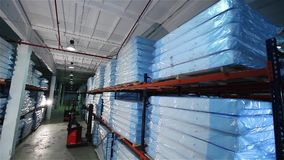 The loader loads a warehouse mattresses, orthopedic mattresses on shelves, a warehouse complete set mattresses, an. Loading of a warehouse mattresses, the loader stock video