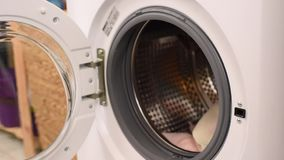 Loading Washing Machine with Dirty Clogthing by Woman Hand stock footage