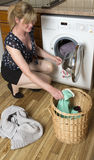 Loading a washing machine. Woman loading a washer dryer machine Stock Images