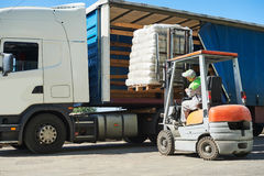 Loading works. Forklift with load and lorry truck. Loading works. Forklift loader moving pallet with load into cargo lorry truck Royalty Free Stock Photography